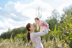 Young beautiful mother holding a baby girl wearing a pink dress in a meadow. On a sunny day royalty free stock image