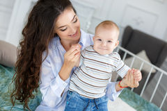 Young beautiful mother holding baby son on her lap, sitting on a bed. Beautiful brunette women with long curly hair, wearing a white shirt and blue jeans Stock Image