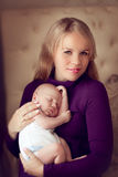 Young beautiful mother holding sleeping newborn baby on hands in Stock Photo