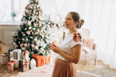Young beautiful mother holds New Year`s decorations standing in the full of light cozy room  next to the New Year`s tree stock photo