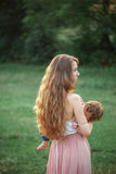 Young beautiful mother hugging her little toddler son against green grass. Happy woman with her baby boy on a summer Stock Photos