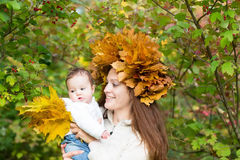 Young beautiful mother in a maple leaf wreath holding a sweet baby girl. Playing with yellow leaves Stock Image