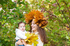Young beautiful mother in a maple leaf wreath holding a sweet baby girl Stock Images