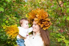 Young beautiful mother in a maple leaf wreath holding a sweet baby girl. Playing with yellow leaves Royalty Free Stock Image