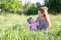 Young beautiful mother playing in the grass with her little baby daughter in panama Royalty Free Stock Images