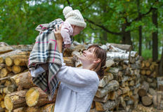 Young beautiful mother playing with her baby in autumn forest. Royalty Free Stock Photos