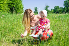 Young beautiful mother playing with her daughter baby in grass outdoors, happy family Stock Photos