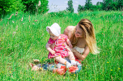 Young beautiful mother playing with her daughter baby in grass outdoors, happy family Royalty Free Stock Image