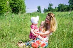 Young beautiful mother playing with her daughter baby in grass outdoors, happy family Royalty Free Stock Photos
