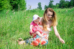 Young beautiful mother playing with her daughter baby in grass outdoors, happy family Royalty Free Stock Photography
