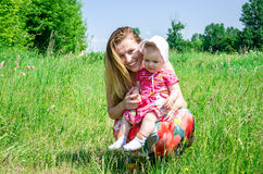 Young beautiful mother playing with her daughter baby in grass outdoors, happy family Stock Photography