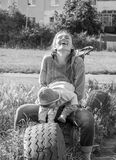 Young beautiful mother playing with her daughter on the playground in the grass sitting on wheels black and white photo Stock Images