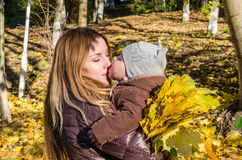 Young beautiful mother playing with her daughter, who is biting mother's nose, in the autumn park among the yellow fallen maple le Stock Photography