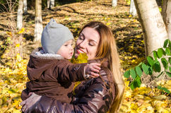 Young beautiful mother playing with her daughter, who is biting mother's nose, in the autumn park among the yellow fallen maple le Royalty Free Stock Photos