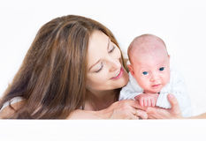 Young beautiful mother playing with her newborn baby laying on h Stock Photos