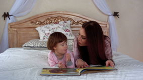 Young beautiful mother reads a book with her little daughter stock video footage