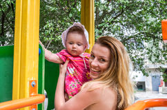 Young beautiful mother riding on a swing at an amusement park with her daughter and baby laugh Royalty Free Stock Image