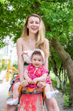 Young beautiful mother riding on a swing at an amusement park with her daughter and baby laugh. Young beautiful mother riding on a swing at an amusement park Stock Photo