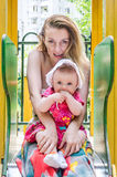 Young beautiful mother riding on a swing at an amusement park with her daughter and baby laugh Stock Image