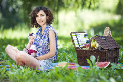 Young beautiful mother sits with her daughter on blanket in park Stock Image
