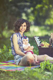 Young beautiful mother sits with her daughter on blanket in park Royalty Free Stock Photo
