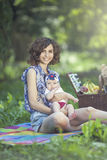 Young beautiful mother sits with her daughter on blanket in park Stock Images