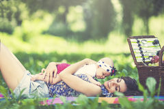 Young beautiful mother sits with her daughter on blanket in park Stock Photography