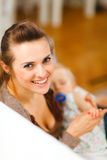 Young beautiful mother with sleeping baby on hands Stock Photo