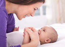 Young beautiful mother smiling and playing with her baby Stock Images