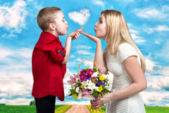 Young beautiful mother and son blow kisses .A woman and a boy with a bouquet,a basket of flowers. Spring concept of family vacati. Spring family holiday concept Royalty Free Stock Photo
