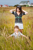 Young beautiful mother with son having fun on the lawn with gree Stock Photography