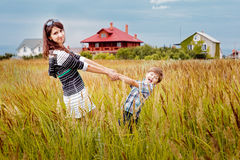 Young beautiful mother with son having fun on the lawn with gree Stock Image