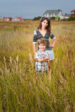 Young beautiful mother with son having fun on the lawn with gree Royalty Free Stock Photo