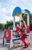 Young beautiful mother in a sweater is playing and riding on a swing with her little baby daughter in a red jacket and hat on the Stock Photos