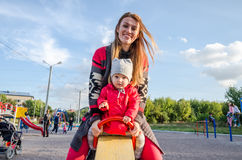 Young beautiful mother in a sweater is playing and riding on a swing with her little baby daughter in a red jacket and hat on the Royalty Free Stock Image