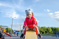 Young beautiful mother in a sweater is playing and riding on a swing with her little baby daughter in a red jacket and hat on the Stock Image