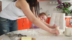 Young beautiful mother teaches daughter prepare dough in the kitchen stock video