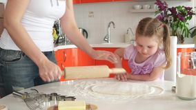 Young beautiful mother teaches daughter prepare dough in the kitchen stock footage