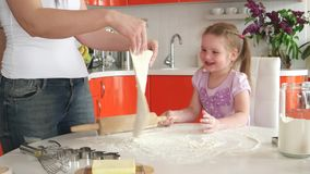 Young beautiful mother teaches daughter to cook in the kitchen stock video