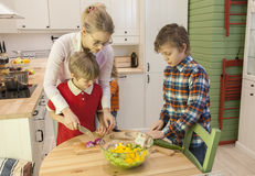 Young beautiful mother with two children cutting vegetables. Young beautiful mother with two children cutting onion and cucumber in the kitchen. Kids helping mom Stock Photography