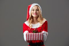 Young and beautiful mrs.Claus dressed in the red robe, Santa`s hat and white gloves holds the Christmas gift in her. Hands on the gray background royalty free stock images