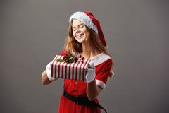 Young and beautiful mrs.Claus dressed in the red robe, Santa`s hat and white gloves holds the Christmas gift in her. Hands and smiles on the gray background stock photo
