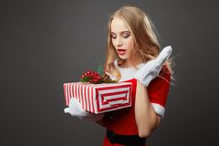 Young and beautiful mrs.Claus dressed in the red robe and white gloves holds the Christmas gift in her hands on the gray royalty free stock photography