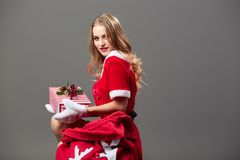Young and beautiful mrs.Santa Claus dressed in the red robe and white gloves sits near the bag with Christmas gifts and stock image