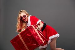 Young and beautiful mrs.Santa Claus in sunglasses dressed in the red robe, white gloves and high heels holds the huge stock photos