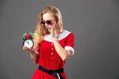 Young and beautiful mrs.Santa Claus in sunglasses dressed in the red robe and white gloves is holding a clock that shows royalty free stock photography