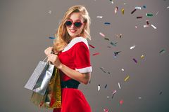 Young and beautiful mrs.Santa Claus in sunglasses dressed in the red robe and white gloves holds the bags with gifts and stock photos