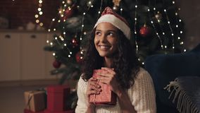 Young Beautiful Mulatto Girl in Santas Hat Sitting under Decorated Cristmas Tree Hugging Red Present Box, Looking Happy stock footage