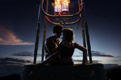 Young beautiful multiethnic couple kissing in the hot air balloon. night and sunrise around. Young beautiful multiethnic couple kissing in the hot air balloon stock image
