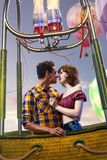 Young beautiful multiethnic couple kissing in the hot air balloon. Very romantic picrure royalty free stock images
